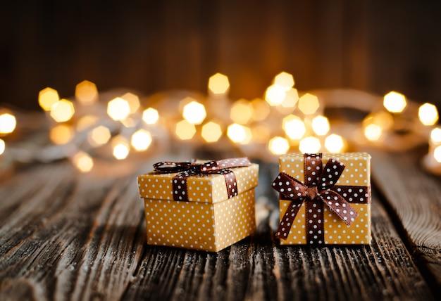 Weihnachtsgeschenkbox lag auf einem holztisch auf einem bokeh von festlichen lichtern.