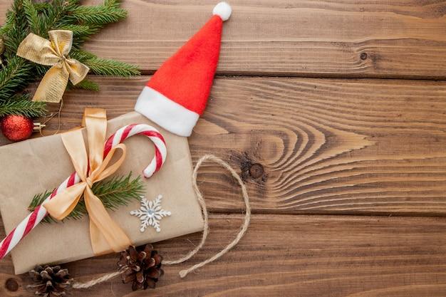 Weihnachtsgeschenkbox, lebensmitteldekor und tannenbaumast auf holztisch. draufsicht mit exemplar