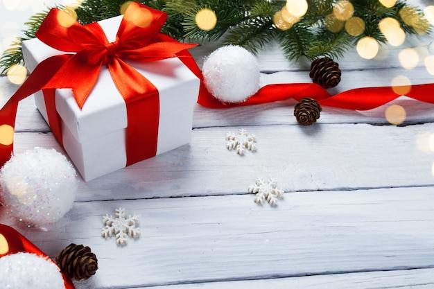Weihnachtsgeschenkbox mit dekoration auf weißem holztisch