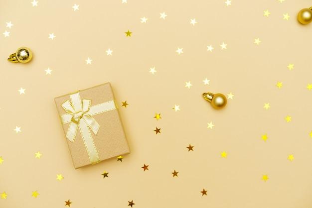 Weihnachtsgeschenkbox mit goldenem band und schleife auf gelbem grund mit weihnachtskugeln und süßigkeitenst...