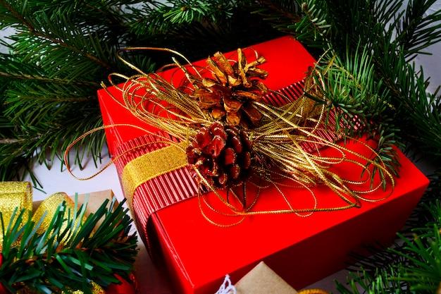 Weihnachtsgeschenkbox mit goldenen tannenzapfen und tannenzweig
