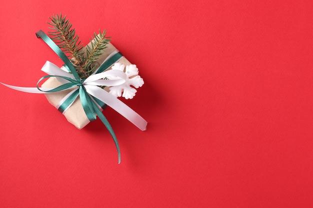 Weihnachtsgeschenkbox mit grünen und weißen bändern auf roter oberfläche. platz für wünsche.