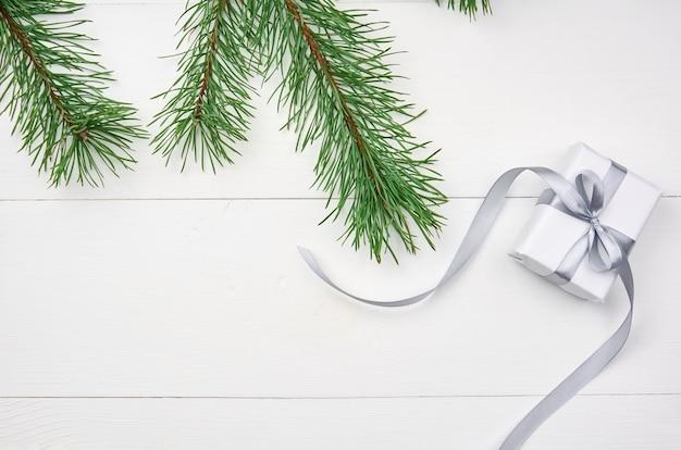 Weihnachtsgeschenkbox mit kiefernzweigen auf weiß