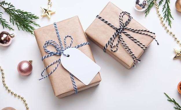 Weihnachtsgeschenkbox mit papiertag und weihnachtsdekorationen auf weißem hintergrund.