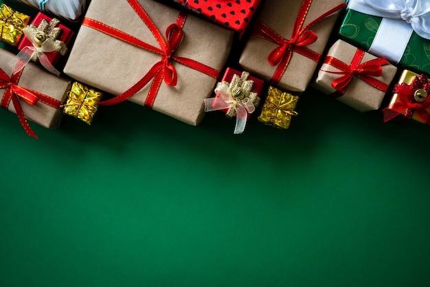 Weihnachtsgeschenkbox mit rotem ball auf grünem hintergrund.