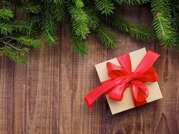 Weihnachtsgeschenkbox mit rotem band auf hölzernem, weihnachtsgeschenken mit dekorationen