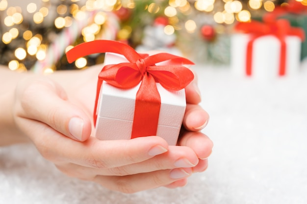 Weihnachtsgeschenkbox mit rotem band und bogen auf dem schnee