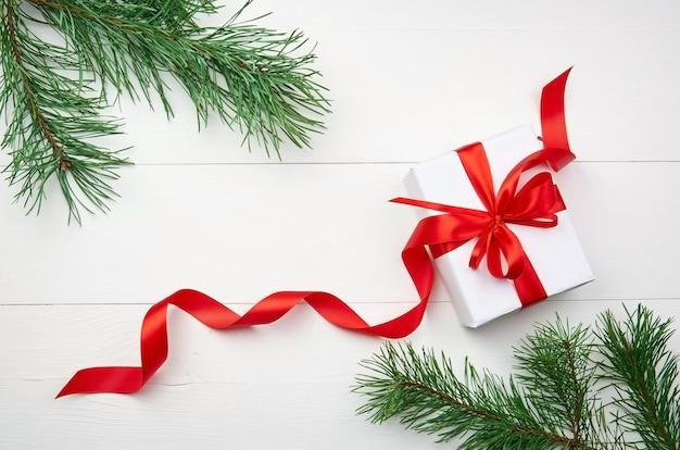 Weihnachtsgeschenkbox mit rotem band und kiefernzweigen auf weiß