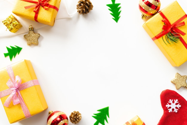 Weihnachtsgeschenkbox mit roten ball- und kiefernkegeln auf weißem hintergrund.