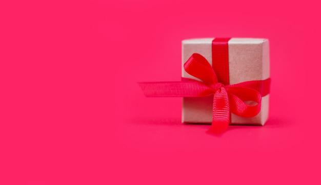 Weihnachtsgeschenkbox mit schleife auf rotem hintergrund