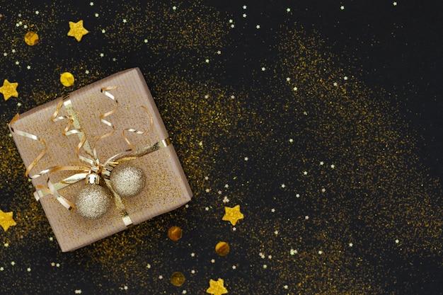 Weihnachtsgeschenkbox oder geschenk verziert goldenes band und zwei kugeln auf schwarzem hintergrund mit funkeln.
