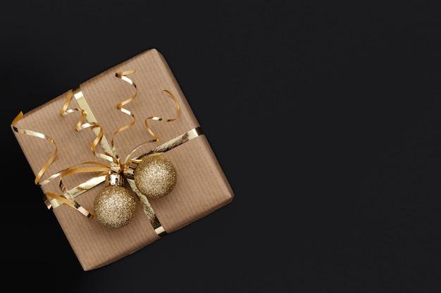 Weihnachtsgeschenkbox oder geschenk verziert goldenes band und zwei kugeln auf schwarzem hintergrund.
