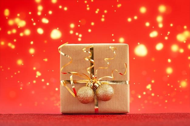 Weihnachtsgeschenkbox oder geschenk verziertes goldenes band und zwei kugeln auf rotem hintergrund. urlaubskonzept.