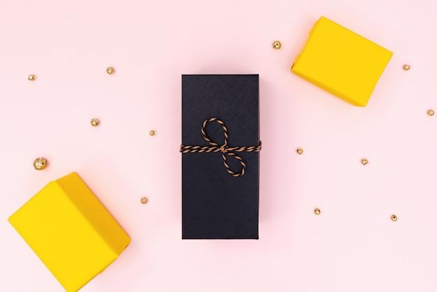 Weihnachtsgeschenkbox, schwarzer und gelber präsentkarton auf rosa