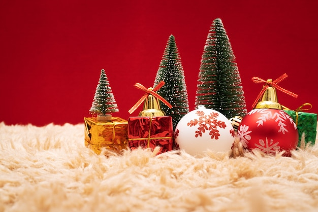 Weihnachtsgeschenkbox und -baum mit goldenen glocken, kiefernkegel auf rotem hintergrund
