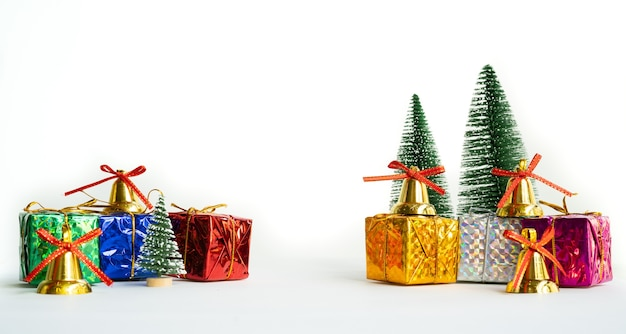 Weihnachtsgeschenkbox und -baum mit goldenen glocken, kiefernkegel auf weißem hintergrund