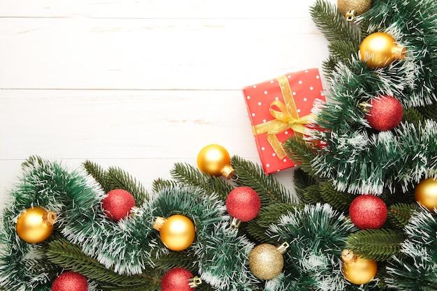 Weihnachtsgeschenkbox und dekorationen auf weißem hölzernem hintergrund. draufsicht.