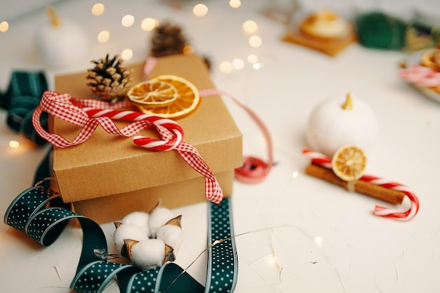 Weihnachtsgeschenkbox und dekorationen auf weißem strukturiertem tisch zuckerstange bunte bänder girlanden trocknen...