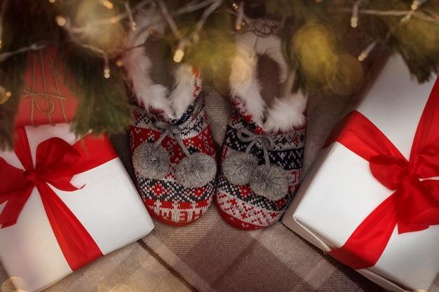 Weihnachtsgeschenkbox und hausschuhe zwischen weihnachtsbeleuchtung