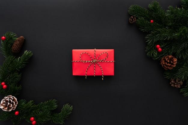 Weihnachtsgeschenkbox und kiefer mit weihnachtsdekoration auf schwarzem hintergrund