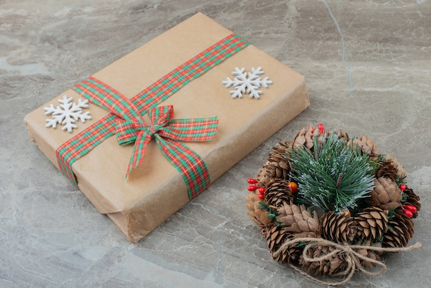 Weihnachtsgeschenkbox und kranz auf marmor.