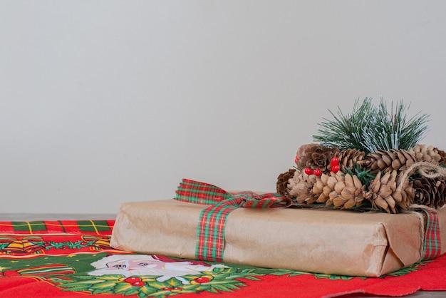 Weihnachtsgeschenkbox und kranz mit tannenzapfen auf marmor.