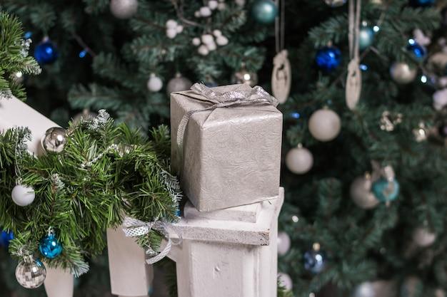 Weihnachtsgeschenkbox und silberbögen auf weihnachtsbaumhintergrund. feiertagsgrußkarte. eingewickelte geschenkbox, weihnachtsverzierungen. neujahrsfeiertagskonzept. handgemachtes geschenk.