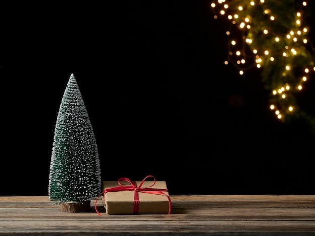 Weihnachtsgeschenkbox und tannenbaum auf holztisch gegen unscharfe festliche lichter, platz für text