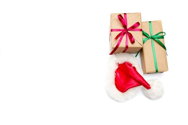 Weihnachtsgeschenkbox und weihnachtsmannhut lokalisiert auf weiß