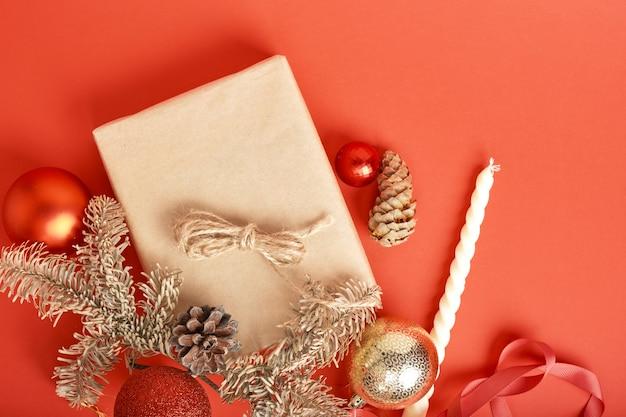 Weihnachtsgeschenkbox verpackt in kraftpapier mit dekoration auf rotem hintergrund draufsicht, weihnachtsdekoration, geschenkverpackung