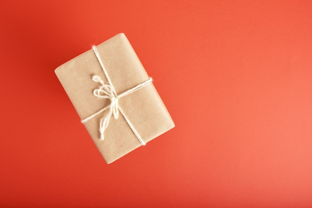 Weihnachtsgeschenkbox verpackt in kraftpapier mit dekoration auf rotem hintergrund draufsicht