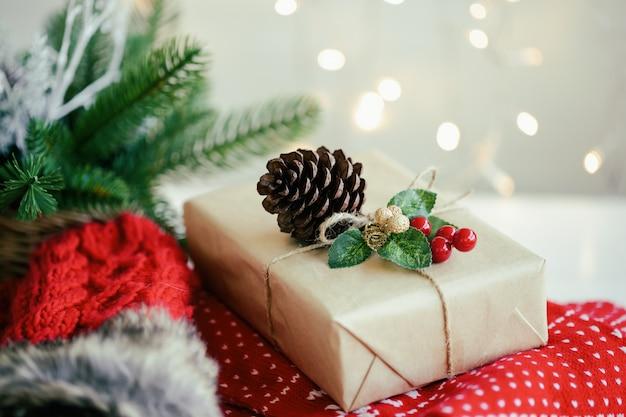 Weihnachtsgeschenkbox verzieren mit den rustikalen seil-, roten und goldenenstechpalmenbällen, die auf roten schal nahe roten strickwarenhandschuhen mit weißem hintergrund und hellem bokeh gesetzt werden. süßer weihnachtshintergrund für weihnachtstapete.
