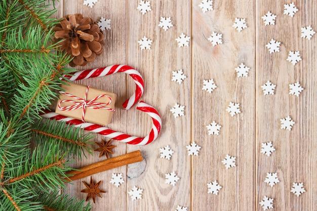 Weihnachtsgeschenkbox, zuckerstange mit schneeflocke und tannenbaumast auf holztisch
