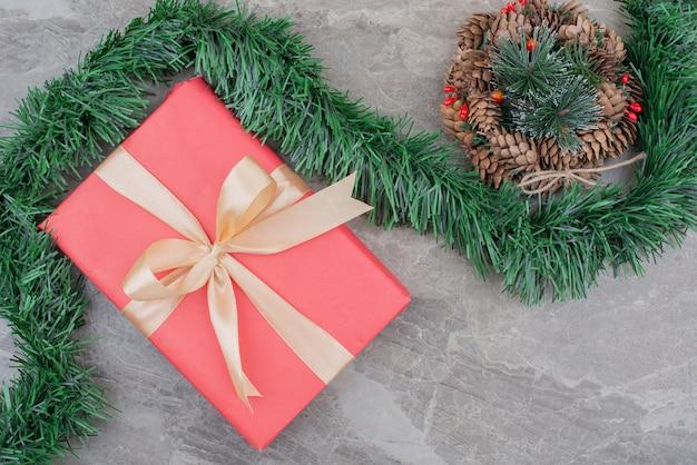 Weihnachtsgeschenkbox, zweig und kranz auf marmor.