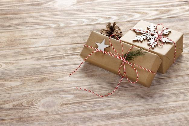 Weihnachtsgeschenkboxen auf holztisch mit schneeflocke. draufsicht mit exemplar