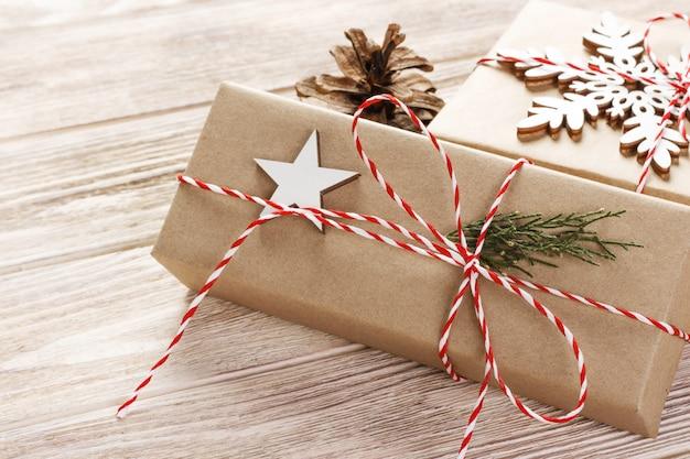Weihnachtsgeschenkboxen auf holztisch mit schneeflocke. draufsicht mit kopienraum