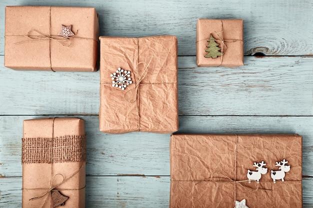 Weihnachtsgeschenkboxen eingewickelt in kraftpapier auf blauem holztisch.