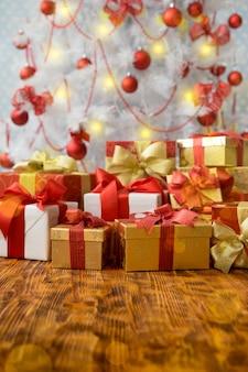 Weihnachtsgeschenkboxen gegen baum mit dekorationen. weihnachtsferienkonzept