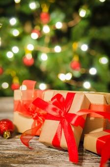 Weihnachtsgeschenkboxen gegen den weihnachtsbaum und das bokeh von funkelnden parteilichtern.