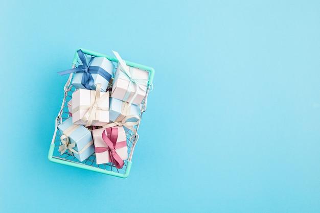 Weihnachtsgeschenkboxen im einkaufskorb auf blauer oberfläche