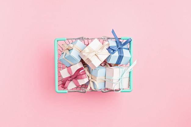 Weihnachtsgeschenkboxen im einkaufskorb auf rosa oberfläche