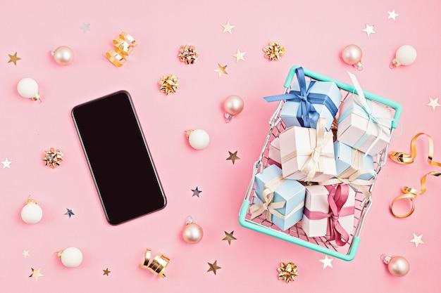 Weihnachtsgeschenkboxen im einkaufskorb und im handy auf rosa oberfläche