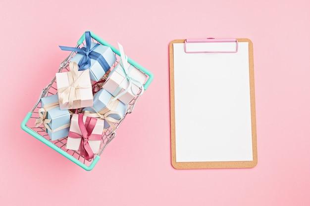 Weihnachtsgeschenkboxen im einkaufskorb und in der zwischenablage auf rosa oberfläche