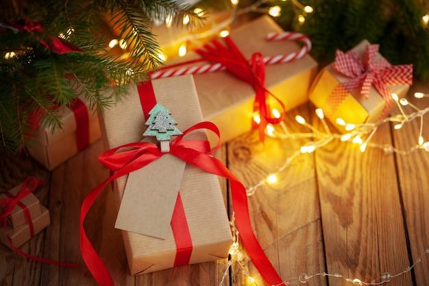 Weihnachtsgeschenkboxen in handwerklicher verpackung auf einem holztisch gegen den weihnachtsbaum. handgefertigte geschenkboxen. weihnachtsfeiertag gemütlich, stimmungskonzept.
