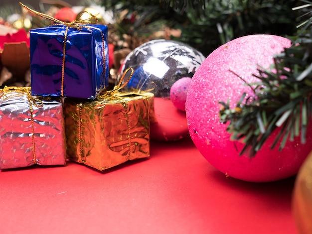 Weihnachtsgeschenkboxen in verschiedenen farben unter weihnachtsbaum auf rotem hintergrund verpackt. . festliche inneneinrichtung.