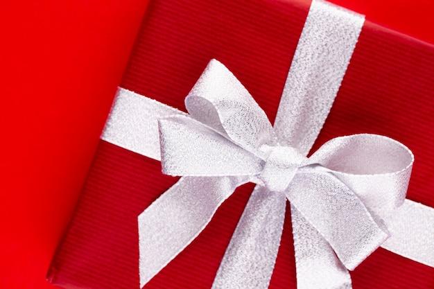 Weihnachtsgeschenkboxen mit bändern auf roter tischplatte.