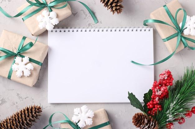 Weihnachtsgeschenkboxen mit grünen bändern auf grauer oberfläche. platz für wünsche.