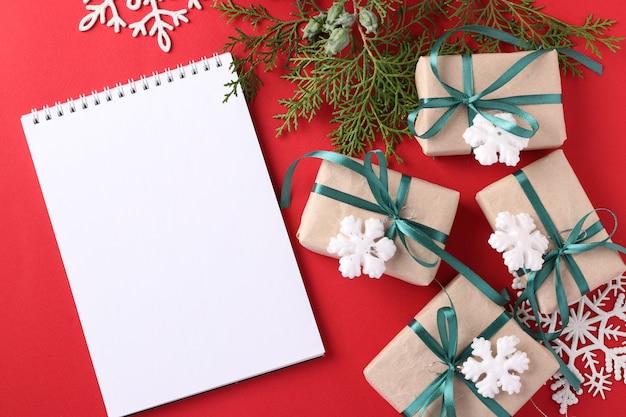 Weihnachtsgeschenkboxen mit grünen bändern auf roter oberfläche. platz für wünsche.
