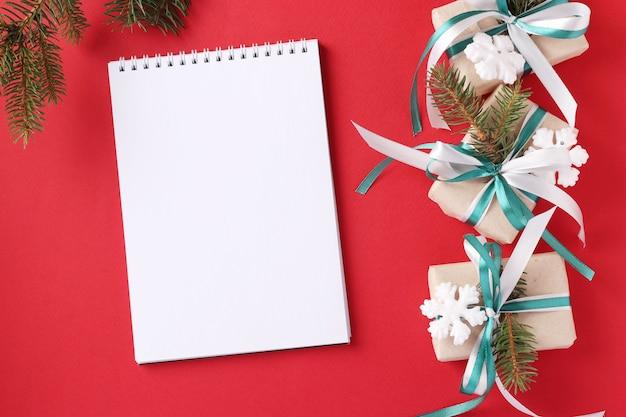 Weihnachtsgeschenkboxen mit grünen und weißen bändern auf roter oberfläche.