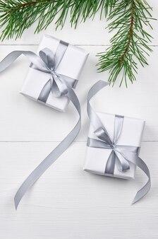 Weihnachtsgeschenkboxen mit kiefernzweigen auf weiß